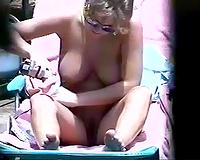 Hidden camera video with a huggy milf sunbathing on a naked beach