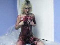 Curly-haired non-professional golden-haired smears her body with paint indoors