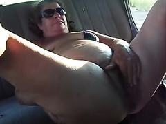 My older plump wifey plays with her hirsute slit in a car