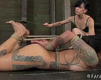 Tattooed brunette hair bitch licks her mistress's toes and love tunnel
