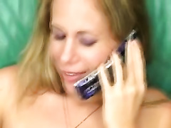 Blonde sweetie plays with her belt during the time that talking on the phone