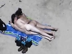 Amateur pair play with every other's genitals on a beach