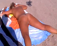 Blonde milf lady on the nudist beach with her legs wide open