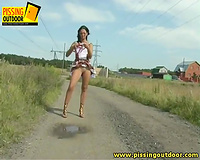 Slim housewife in lovely suit pisses on the road in the countryside