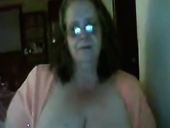 Slutty granny shows her large love bubbles and smokes in front of a web camera