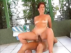 Short haired older woman is having sex with a youthful fellow by the pool