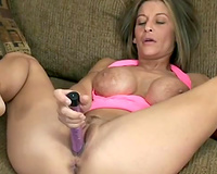 Fake-boobed golden-haired mommy satisfies herself with the assist of a dildo