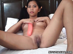 Oriental hoochie with pigtails copulates her snatch with gigantic dildo