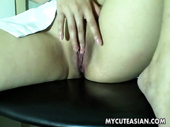 Solo scene with a pigtailed Asian beauty masturbating indoors