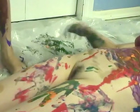 Two cute women smear each other's bodies with paints