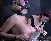 Red-haired domina sticks needles below her slave's fingernails